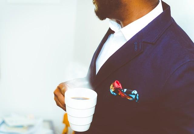 スーツ姿でコーヒーを飲む男性