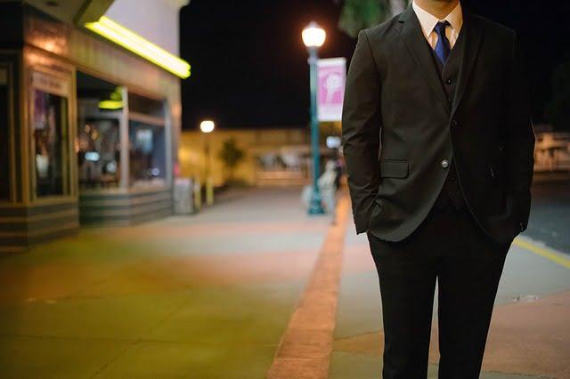 道路に立つスーツを着た男性
